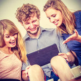 Friends relaxing browsing internet on tablet. Royalty Free Stock Image