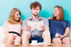 Friends relaxing browsing internet on tablet. Royalty Free Stock Photos