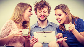 Friends relaxing browsing internet on tablet. Stock Images
