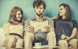 Friends relaxing browsing internet on tablet. Royalty Free Stock Photo