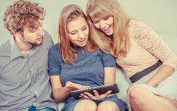 Friends relaxing browsing internet on tablet. Royalty Free Stock Images