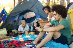 Friends relaxing at campsite Stock Image