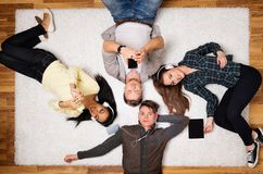 Friends relaxing on a carpet with gadgets. Happy multiracial friends relaxing on a carpet with gadgets Stock Image