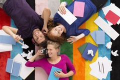 Friends relaxing on colorful carpet. Shot of three friends relaxing on a colorful carpet surrounded by notebooks Stock Images
