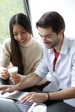 Friends relaxing with a cup of coffee and  working on laptop Royalty Free Stock Images