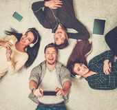 Friends relaxing with gadgets. Happy multiracial friends relaxing on a carpet with gadgets Stock Photos