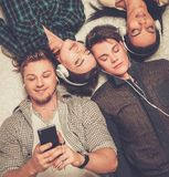 Friends relaxing with gadgets. Happy multiracial friends relaxing on a carpet with gadgets Royalty Free Stock Photo