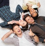 Friends relaxing with gadgets. Happy multiracial friends relaxing on a carpet with gadgets Royalty Free Stock Photography