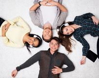 Friends relaxing  with gadgets. Happy multiracial friends relaxing on a carpet with gadgets Royalty Free Stock Photos