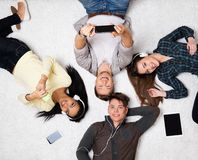 Friends relaxing  with gadgets. Happy multiracial friends relaxing on a carpet with gadgets Stock Photo