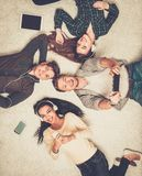 Friends relaxing  with gadgets. Happy multiracial friends relaxing on a carpet with gadgets Stock Images