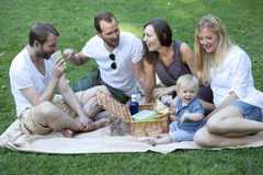 Friends relaxing in park with baby Royalty Free Stock Photography