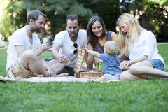 Friends relaxing in park with baby Stock Image
