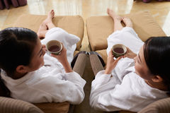 Friends Relaxing in Spa Salon. High angle view of two pretty friends drinking herbal tea and chatting animatedly while relaxing in spa salon Royalty Free Stock Photo