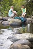 Friends Relaxing By Stream Royalty Free Stock Photography