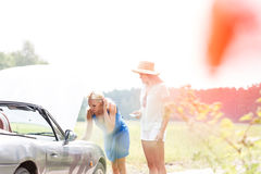 Friends repairing broken down car on sunny day Royalty Free Stock Images