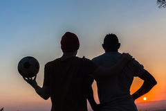 Friends Respect Silhouetted Football. Two male plus football friends together silhouetted by the sunset skyline Stock Photos