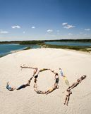 Friends at rest. Image of word joy made up of young people sunbathing with sea and sky at background Stock Image