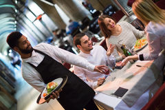 Friends in restaurant and black waiter Stock Photos
