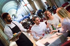 Friends in restaurant and black waiter stock photography