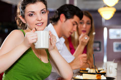 Friends in Restaurant eating and drinking. Three friends in a restaurant or diner eating cheesecake and drinking coffee Royalty Free Stock Photo