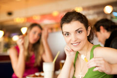 Friends in Restaurant eating fast food Royalty Free Stock Photography