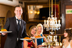 Friends in restaurant, waiter served the dinner Stock Photo