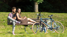 Friends resting on a bench in park with bikes close by Stock Photo