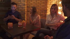 Friends is resting in a cafe. A company of young people is resting at a table in the club. Students relax in in the evening. Two young couples in a cafe stock video