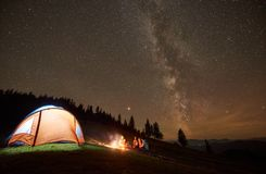 Friends resting beside camp, campfire under night starry sky stock photography