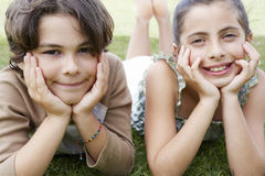 Friends Resting Chin In Hands While Lying On Grass Stock Photo