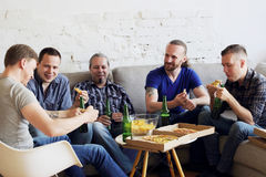 Friends resting at home. Group of men drinking beer, eating pizza, talking and smiling while resting at home on couch behind TV Royalty Free Stock Photos
