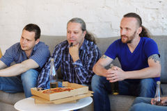 Friends resting at home. Group of men drinking beer, eating pizza, talking and smiling while resting at home on couch behind TV Stock Image