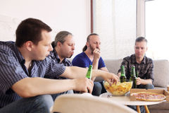 Friends resting at home. Group of men drinking beer, eating pizza, talking and smiling while resting at home on couch behind TV Stock Photos