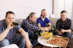 Friends resting at home. Group of men drinking beer, eating pizza, talking and smiling while resting at home on couch behind TV Royalty Free Stock Photography