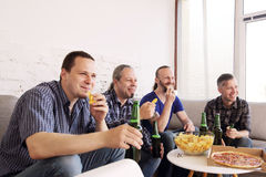 Friends resting at home. Group of men drinking beer, eating pizza, talking and smiling while resting at home on couch behind TV Royalty Free Stock Photo