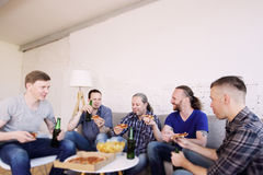 Friends resting at home. Group of men drinking beer, eating pizza, talking and smiling while resting at home on couch behind TV Royalty Free Stock Images