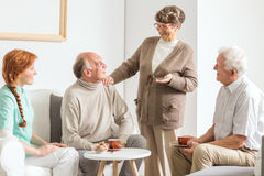 Friends at retirement club. Group of older friends and young nurse spending time at retirement club royalty free stock image