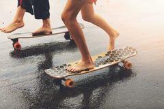 Friends riding longboards on wet city street Stock Photos