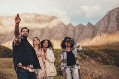 Friends on road trip admiring a landscape. Friends on roadtrip. Group of men and women standing in nature. Man showing something to his female friends while a Stock Photo