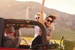 Friends On Road Trip Driving In Convertible Car Stock Photo