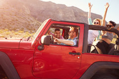 Friends On Road Trip Driving In Convertible Car Stock Photography