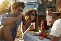 Friends on a road trip having a picnic beside a camper van Royalty Free Stock Photos