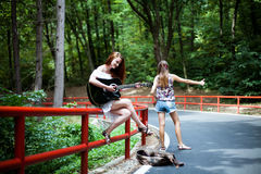 Friends in a road trip hitchhiking. Girl playing guitar Stock Photo