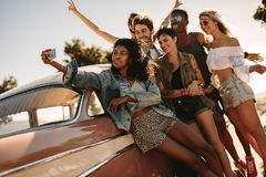 Friends on road trip posing for a selfie. Group of young people on a road trip standing together by the car and taking selfie. Young men and women taking a Royalty Free Stock Images