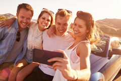 Friends On Road Trip Sit On Convertible Car Taking Selfie Stock Images