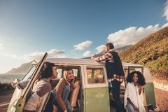 Friends on roadtrip relaxing by the van. Group of men and women travelling together in an old minivan Stock Image