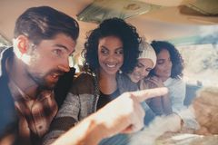Friends discussing roadtrip route using map Stock Images