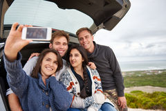 Friends on a roadtrip together taking a selfie. Group of friends at the back of their car taking a selfie while on a roadtrip stock photo