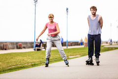 Friends rollerblading together have fun in park. Stock Photography